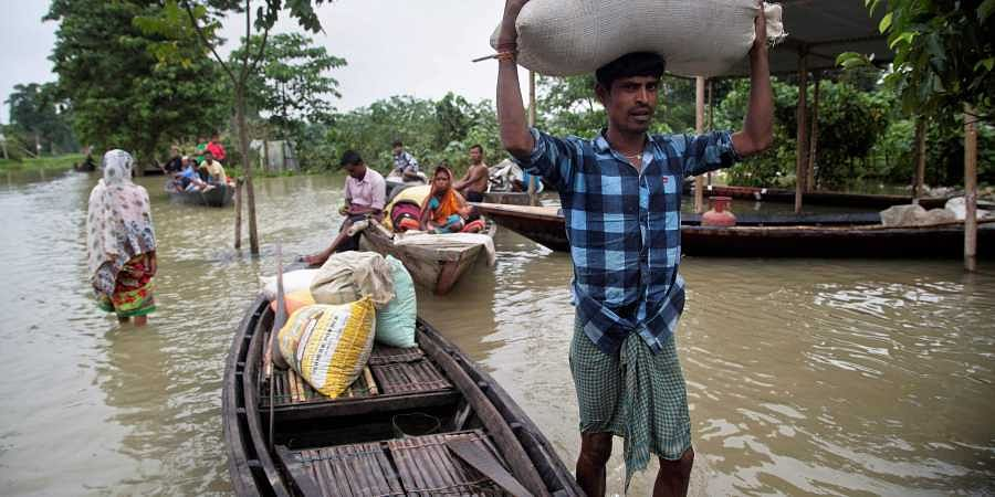 A flood affected villager carries food grains on his head in Burha Burhi village, east of Gauhati, Assam.