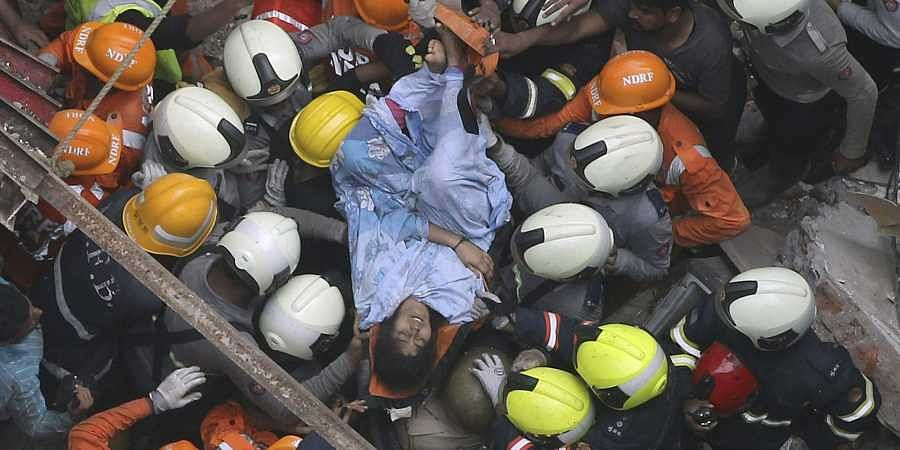 Rescuers carry out a survivor from the site of a building that collapsed in Mumbai, India, Tuesday, July 16, 2019.