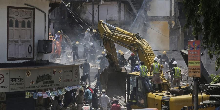 Rescue workers clear debris from the site of a building collapse. (Photo | AP)