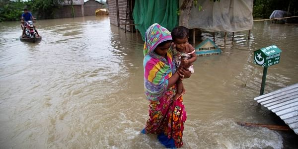 A woman carrying her child wades through flood waters in Burha Burhi village , east of Gauhati, Assam. (Photo   AP)