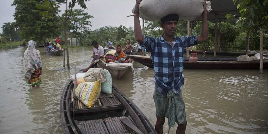 A flood affected villager carries food grains on his head in Burha Burhi village, east of Gauhati in Assam