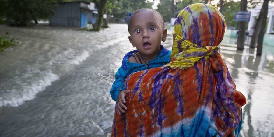 An woman carrying her child wades through a flooded road in Jhargaon, east of Gauhati, Assam.