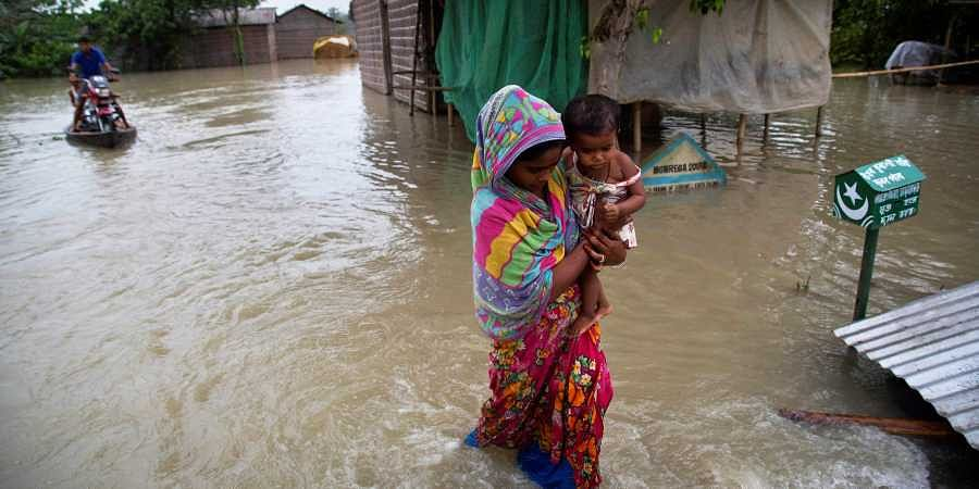 A woman carrying her child wades through flood waters in Burha Burhi village , east of Gauhati, Assam.