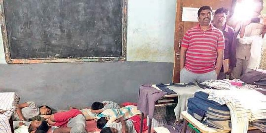 Collector G Veerapandian expresses disappointment over students sleeping on the floor inside the classrooms without bedsheets at the AP Tribal Welfare Gurukul Boys' School in Panyam on Monday night.