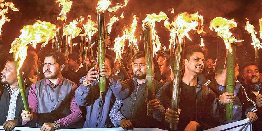 Activists of All Assam Students Union and other organisations at a torch light rally in Guwahati