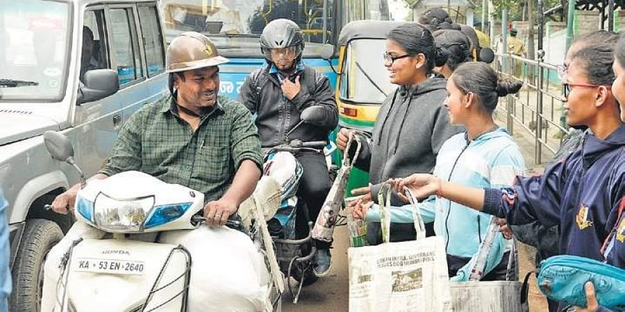 A group of college students requests motorists to use environment-friendly paper bags, instead of plastic bags, near KR Circle in Bengaluru on Wednesday (Photo | Shriram BN, EPS)
