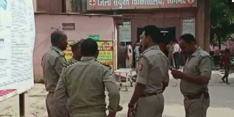 Police wait outside the Sonbhadra district hospital after casualities were brought here following Wednesday's clash
