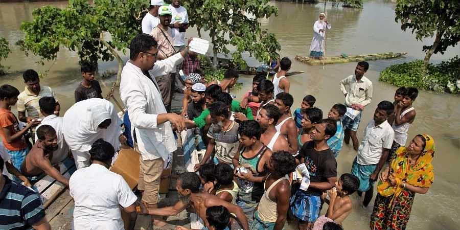 Medical officers distribute medicines to flood victims in Gagalmari, Assam.