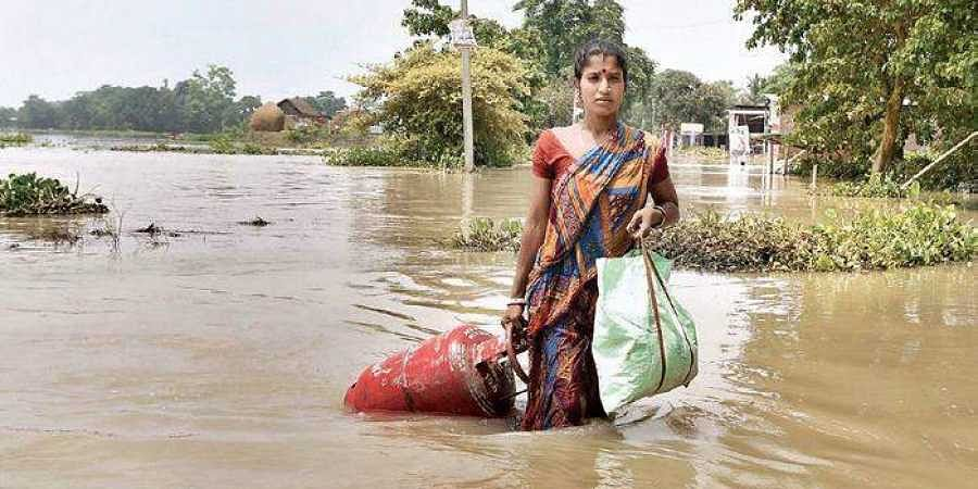 A woman carries her belongings from a flood affected area to a safer place, following heavy monsoon rain in Morigaon district of Assam on Friday