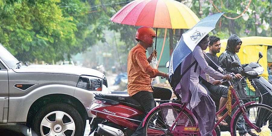 Commuters take cover from rains in Bhubaneswar.