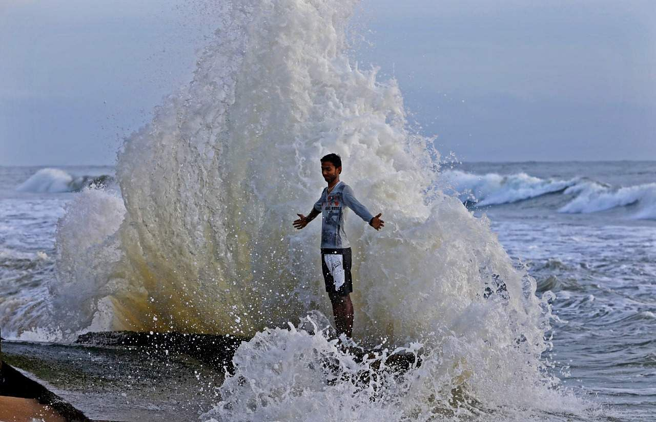 A lad from Tamilnadu, unmindful of warnings to not enter the sea during a strong tide, poses at Puthuvype beach in Kochi, Kerala. There is no sign of caution for tourists at the place. (Photo | Arun Angela, EPS)