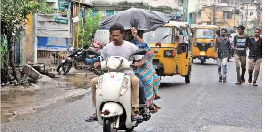 A woman pillion rider uses umbrella to protect herself from rain in Rajamahendravaram on Saturday