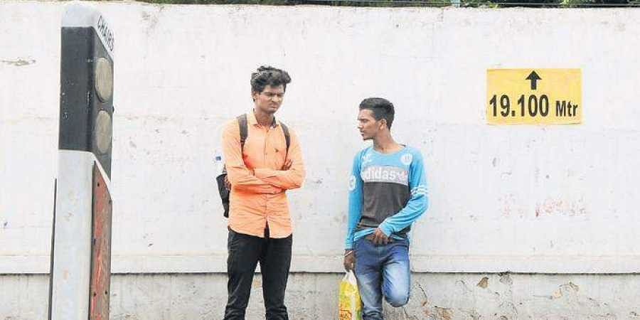 Two pedestrians stand beside a marking, made for extension of roads under the Skyway project, in Secunderabad Cantonment on Wednesday