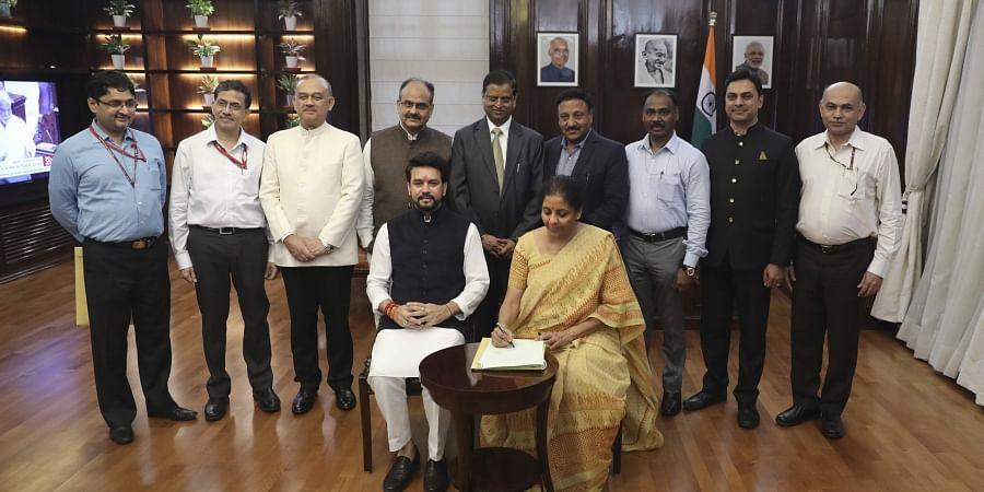 Finance Minister Nirmala Sitharaman, seated right, signs the Indian federal budget after giving final touches, as MoS Finance and Corporate Affairs Anurag Thakur, seated left, watches along with finance budget team at her office in New Delhi, India, July