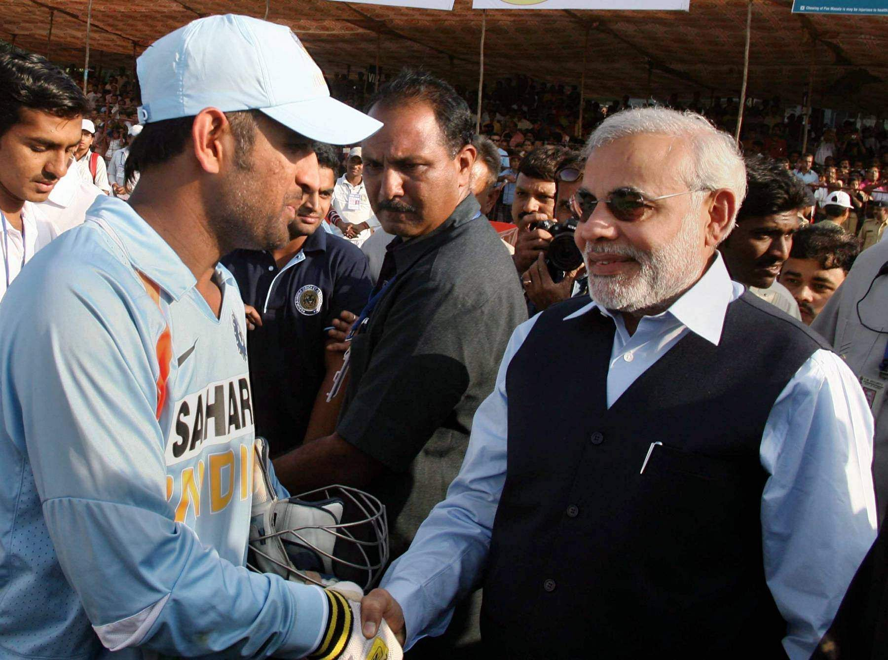 Then Gujarat CM Narendra Modi shakes hands with skipper MS Dhoni as he greets Indian team for their win over England in the first ODI at the Madhavrao Scindia cricket ground.