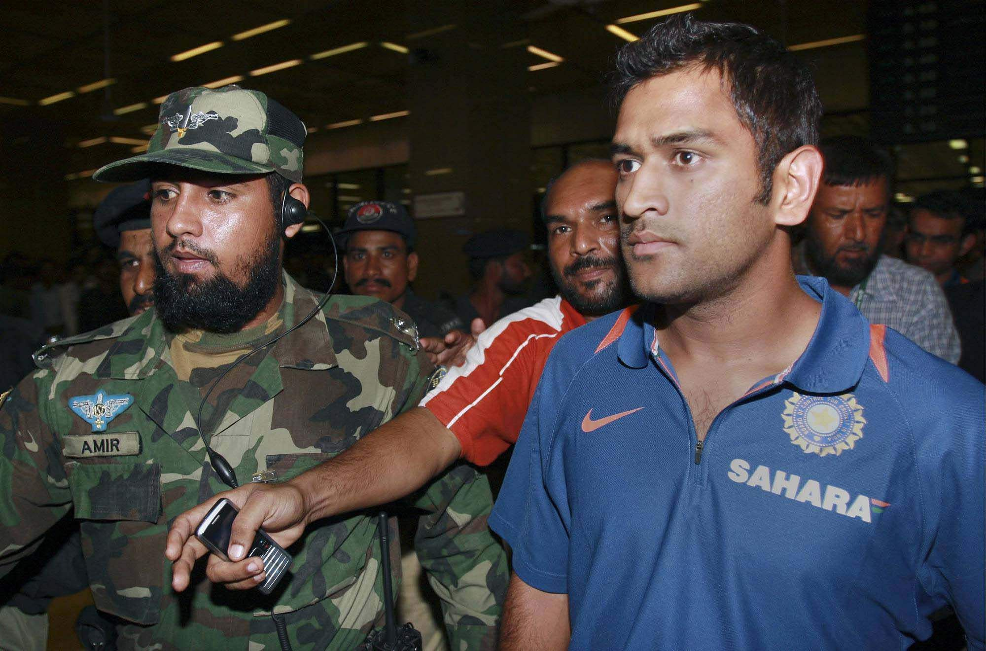 Then Indian skipper MS Dhoni is escorted by Pakistani security officers upon his arrival at Quaid-e-Azam International airport in Karachi, Pakistan in 2008.
