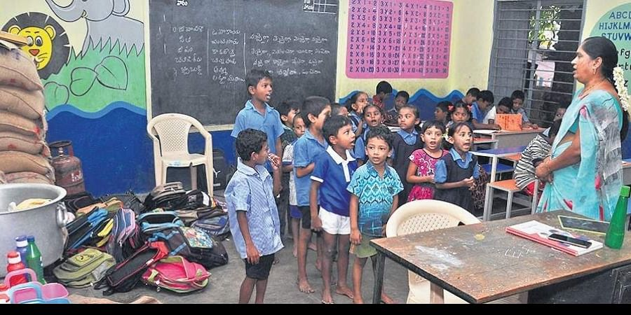 A teacher takes a class on happiness in a classroom that looks like filled with bags and utensils at a school in Vijayawada.