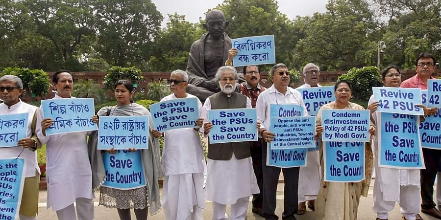 TMC MPs hold banners as they protest in front of Gandhi statue in Parliament over disinvestment in public sector undertakings (PSUs) in New Delhi on 9 July 2019. (Photo | PTI)