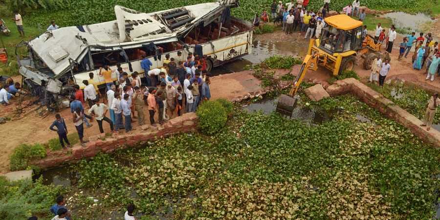 People look on at the mangled remains of a bus after it skidded off the six-lane Yamuna Expressway and fell into a large drain near Agra on 8 July 2019. (Photo | PTI)