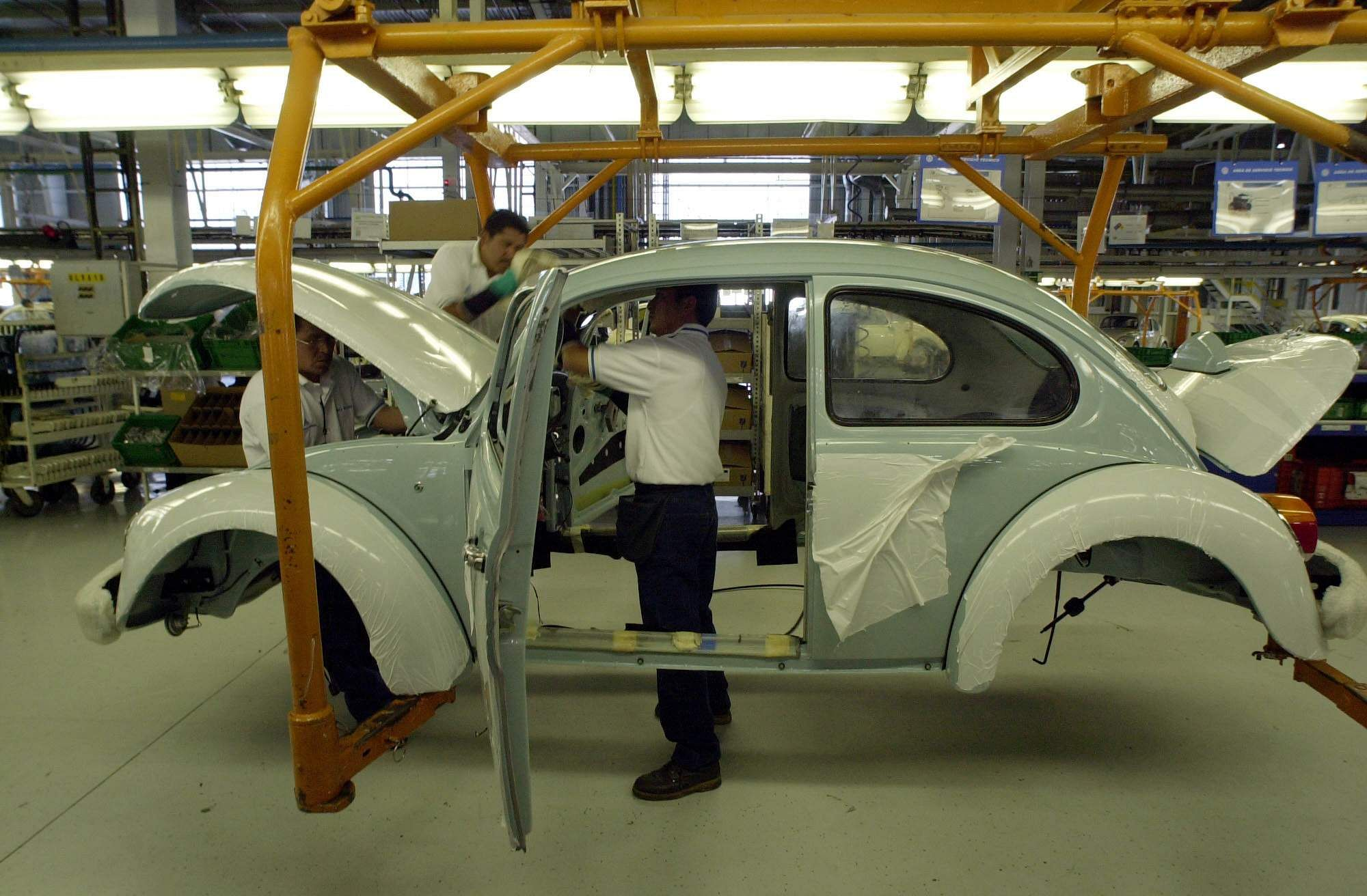 In this July 21, 2003 file photo, Volkswagen employees work in the assembly plant of the Volkswagen sedan 'last edition,' at the VW plant in Puebla, 65 miles (105 kms) southeast of Mexico City where it will stop producing the cult classic bug on July 30th. (File Photo   Associated Press)