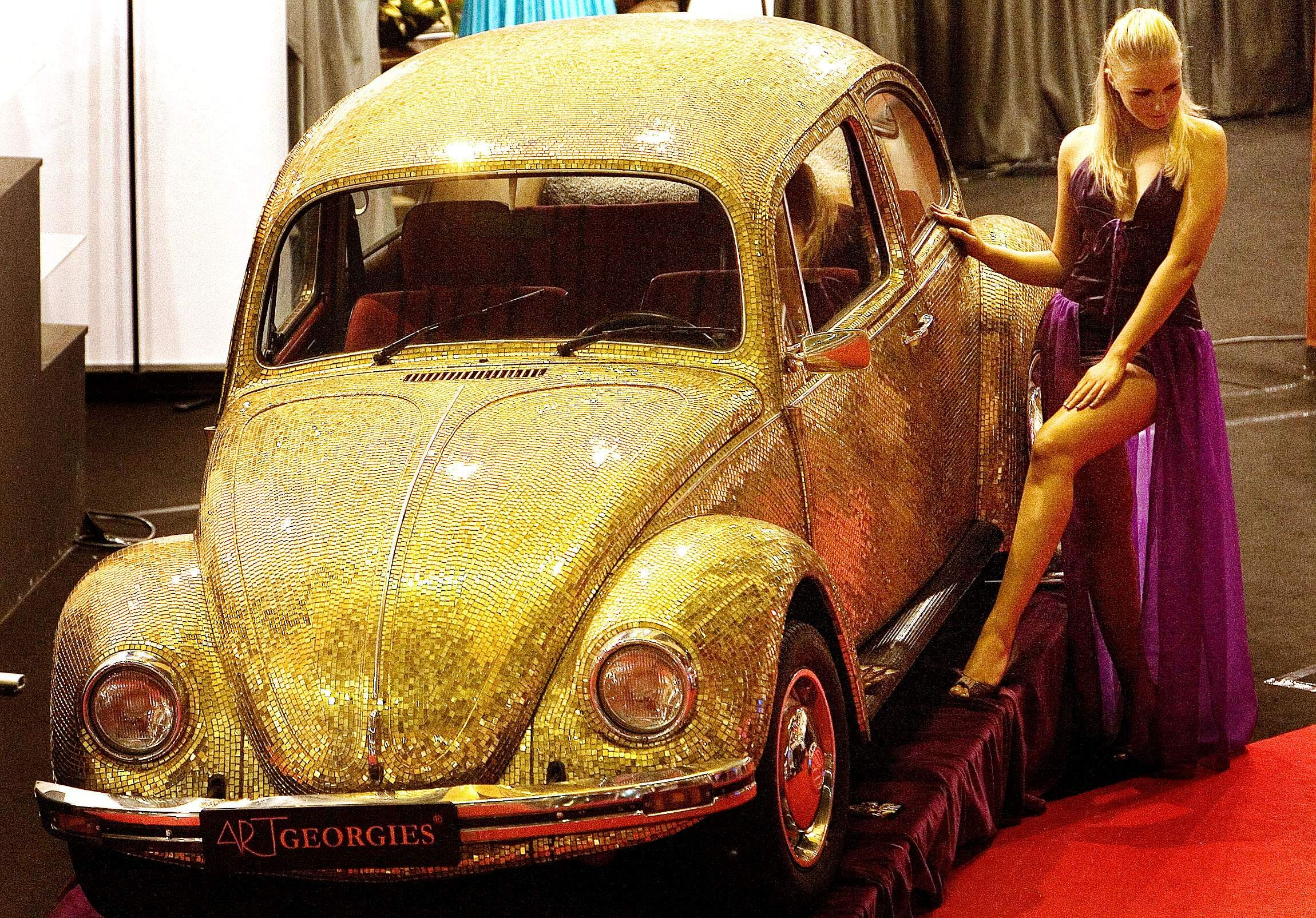 In this Dec. 8 2007 file photo, a model poses next to a 1968 Volkswagen Beetle covered in tiles made of a blend of 18 karat gold and glass at the annual Luxury Show in Bucharest, Romania. The car is functional and on sale for 60,000 euros, $88,000. However it is not street legal in Romania because of the nature of its paint. (File Photo   Associated Press)