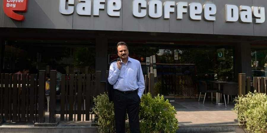 VG Siddhartha in front of a Cafe Coffee Day.