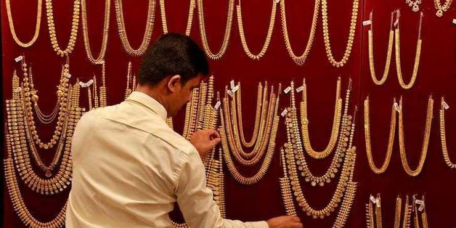 A salesman arranges gold ornaments, on a display board, inside a jewellery showroom