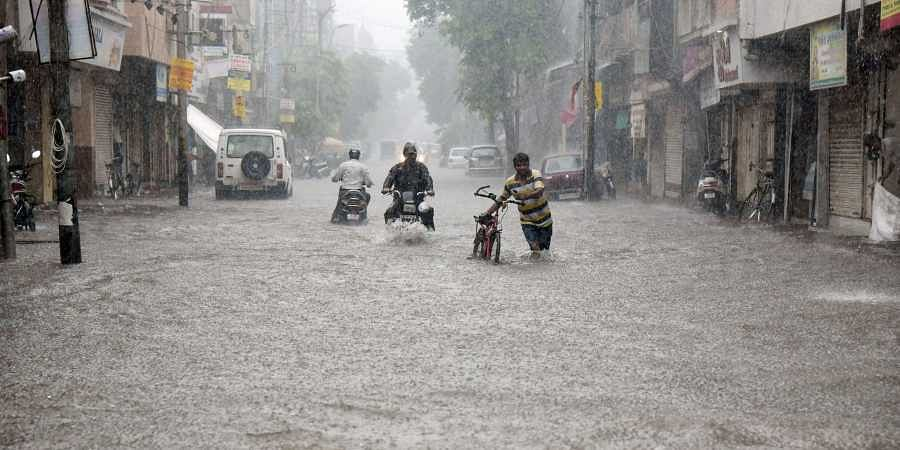 Commuters move slowly through a flooded street following incessant rains in Vadodara Wednesday July 31 2019.