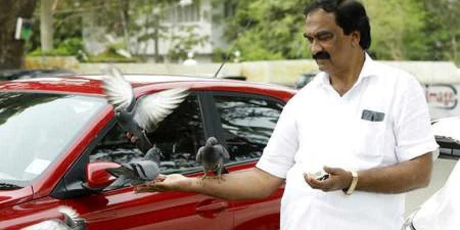 P H Abdul Salam feeding pigeons  near Fort Kochi beach.