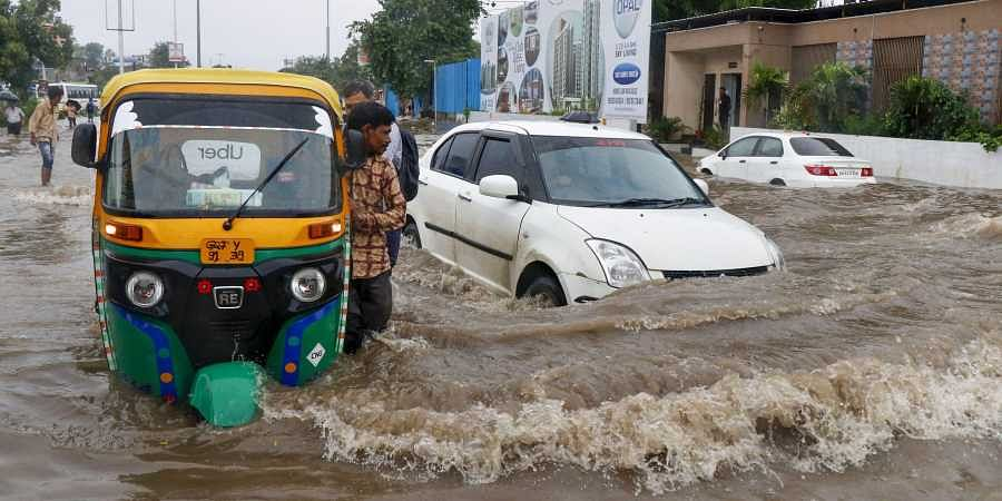 Vehicles wade across a waterlogged street following heavy rainfall in Ahmedabad, Gujarat on Aug 10 2019. (Photo | PTI)