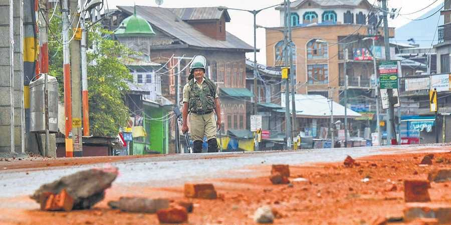 A security personnel stands guard during curfew-like restriction on the fifth consecutive day in Srinagar