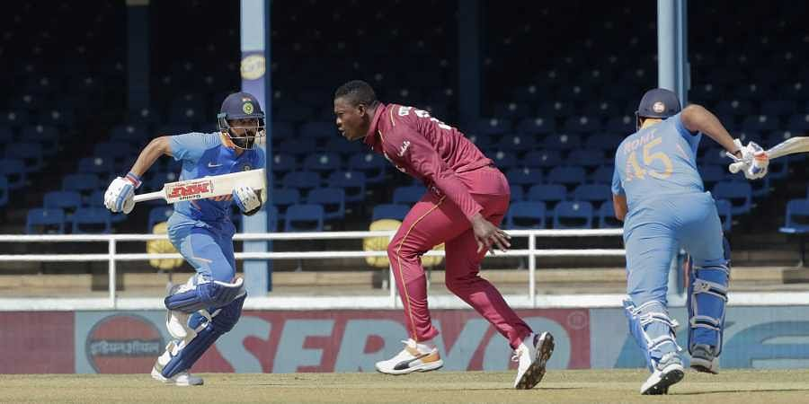 India captain Virat Kohli, left, and Rohit Sharma, right, run between the wickets as West Indies bowler Sheldon Cottrell looks on.
