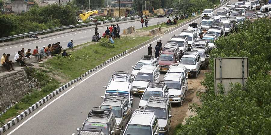 Taxis stand parked during restrictions in Jammu