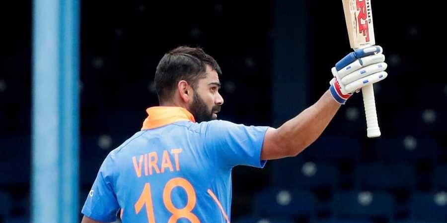 India's captain Virat Kohli rises his bat as he celebrates his century against West Indies.