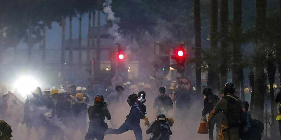 A protester throws a tear gas canister fired by riot policemen during the anti-extradition bill protest in Hong Kong.