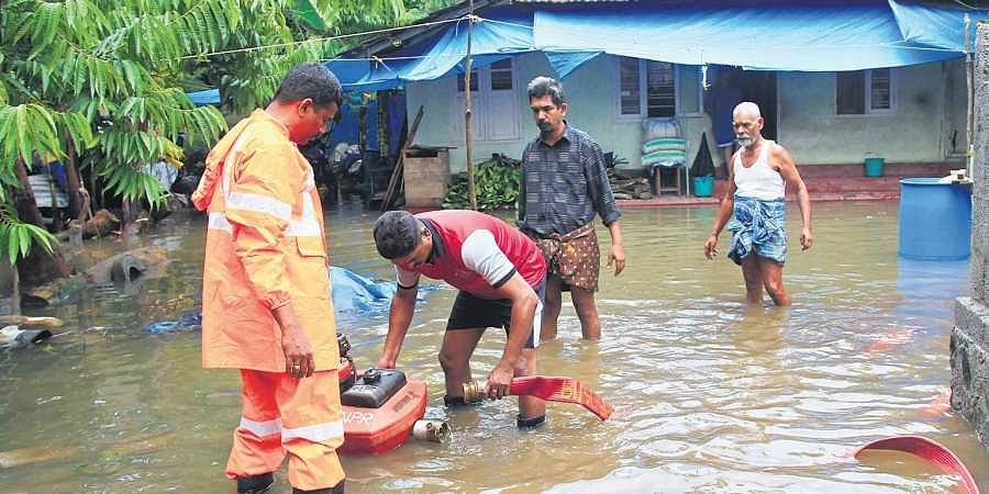 Vedimara resident Abdul Khader along with Fire and Rescue Services officials pump out water in front of his house in North Paravoor.