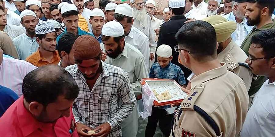 Srinagar Police and administrative officers offer sweets to people after offering Eid al-Adha prayers in Srinagar on Monday