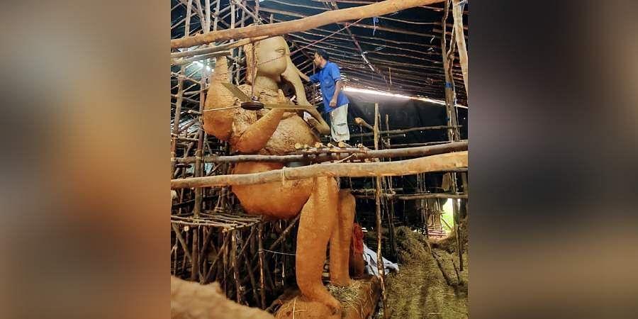 An Indian artist works on eco-friendly figures of Hindu deity Ganesha at Visakhapatnam