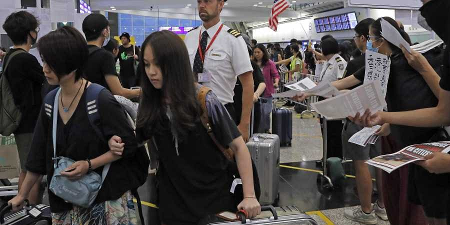 Passengers and flight crew arrive at Hong Kong International Airport, Monday, Aug. 12, 2019. One of the world's busiest airports canceled all flights after thousands of Hong Kong pro-democracy protesters crowded into the main terminal Monday afternoon.