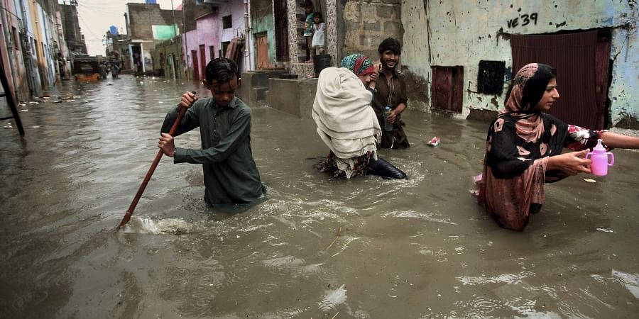 A family wades through a flooded street caused by heavy monsoon rains, in Karachi