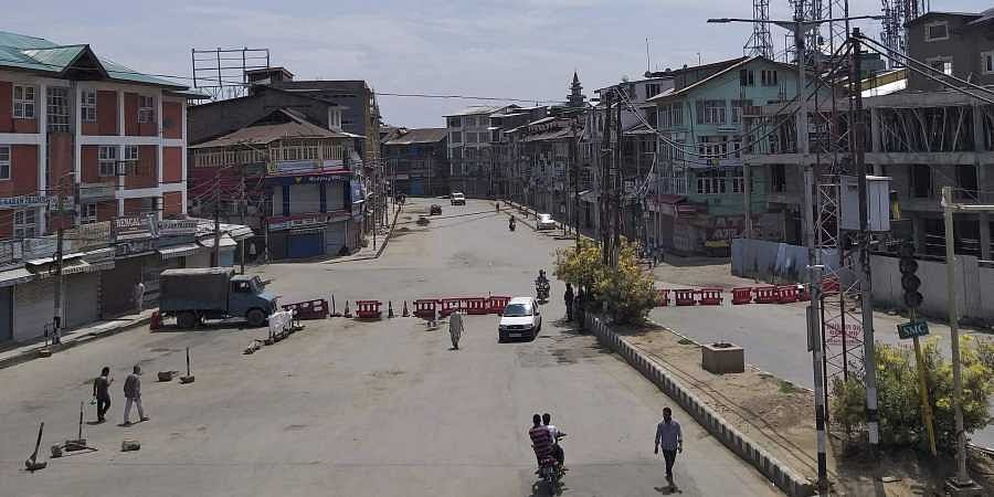 Pedestrians move on a deserted street in Srinagar on Thursday 8th August 2019