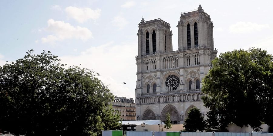 Workers install high fences on a bridge around Notre Dame cathedral in Paris