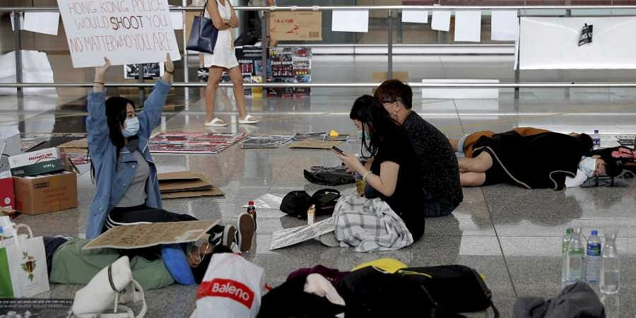 A protester shows a placard to travellers as they continue their sit-in rally at the airport in Hong Kong.