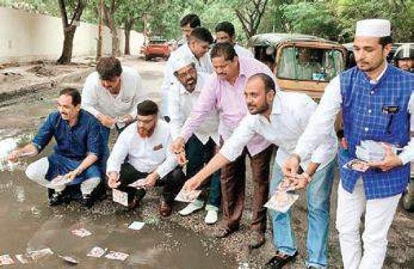 Telangana Congress workers dumppictures of CM KCR, KTR in potholes