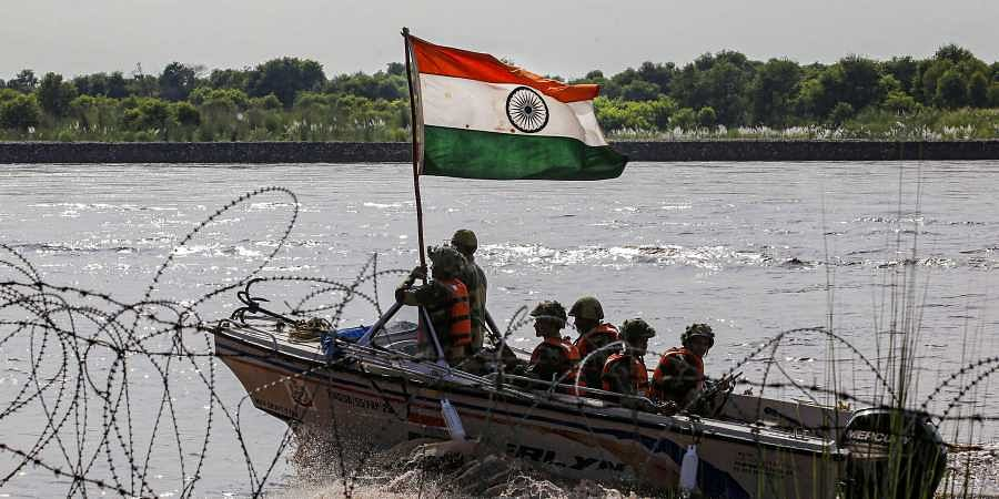 BSF soldiers on a boat patrol the Chenab river on the eve of Independence Day along the India Pakistan border in Akhnoor about 55 km from Jammu