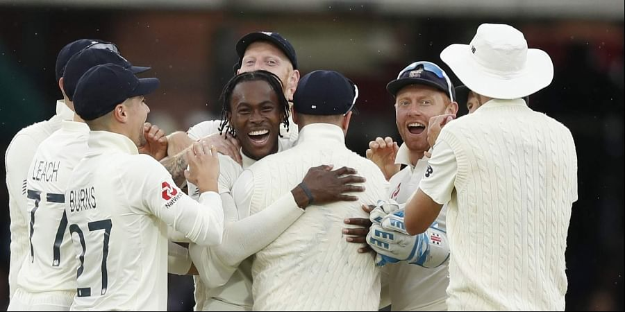 England's Jofra Archer, centre, celebrates after taking the wicket of Australia's Cameron Bancroft.