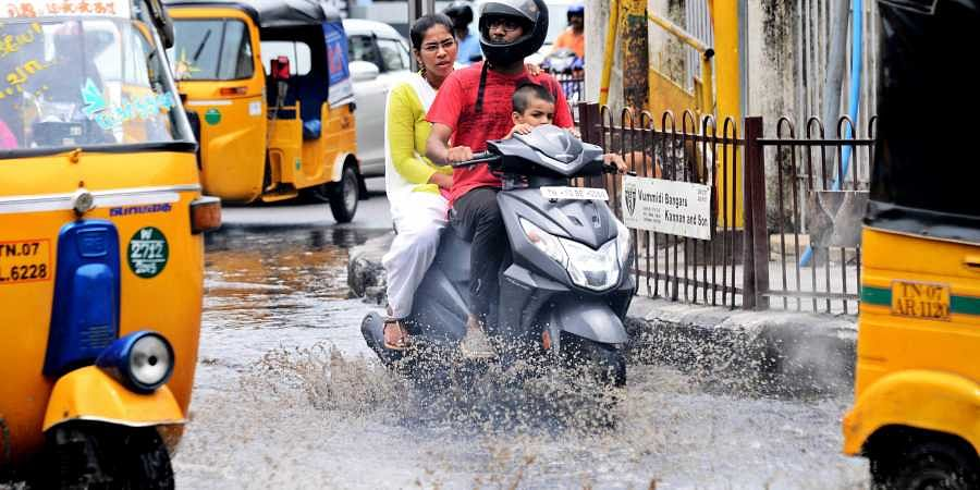 Commuters face a harrowing time crossing a water logged street near Gemini flyover in Chennai on Sunday.