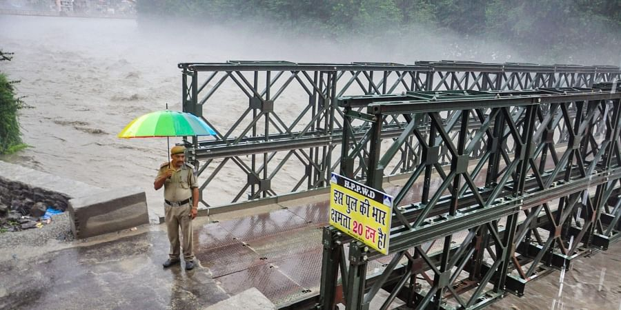 A policeman stands at the entry point of the bypass road bridge that was closed for the vehicular traffic as Beas river was flowing above the danger mark in Kullu Saturday August 17, 2019.