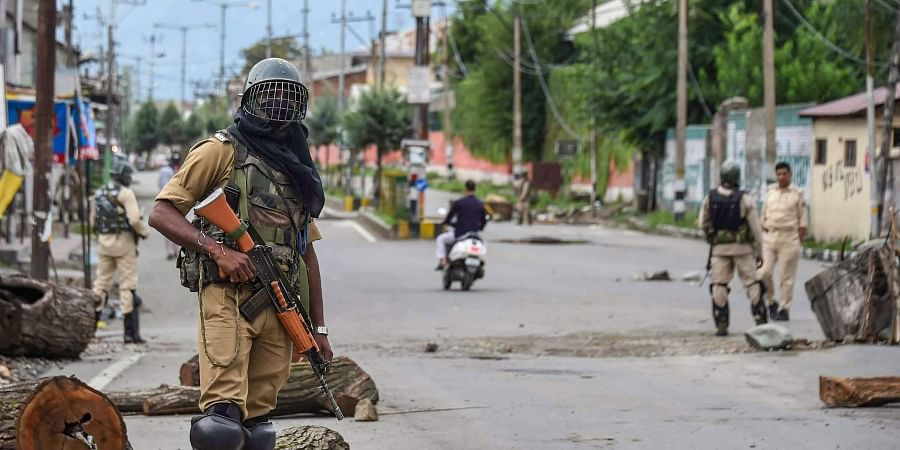 Security personnel stand guard at a check-point during curfew like restrictions on the 13th consecutive day following the abrogation of the provisions Article 370 in Jammu and Kashmir in Srinagar Saturday August 17 2019.