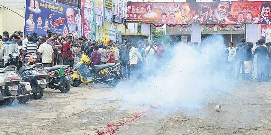 Fans burst crackers in front of a cinema theatre just before film star Rajnikanth's Kalaa is shown on the first day of release